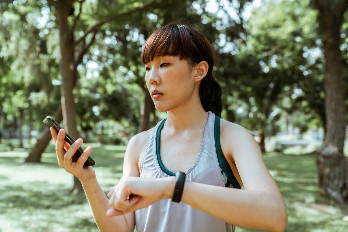 Concentrated young Asian woman using smartphone in park